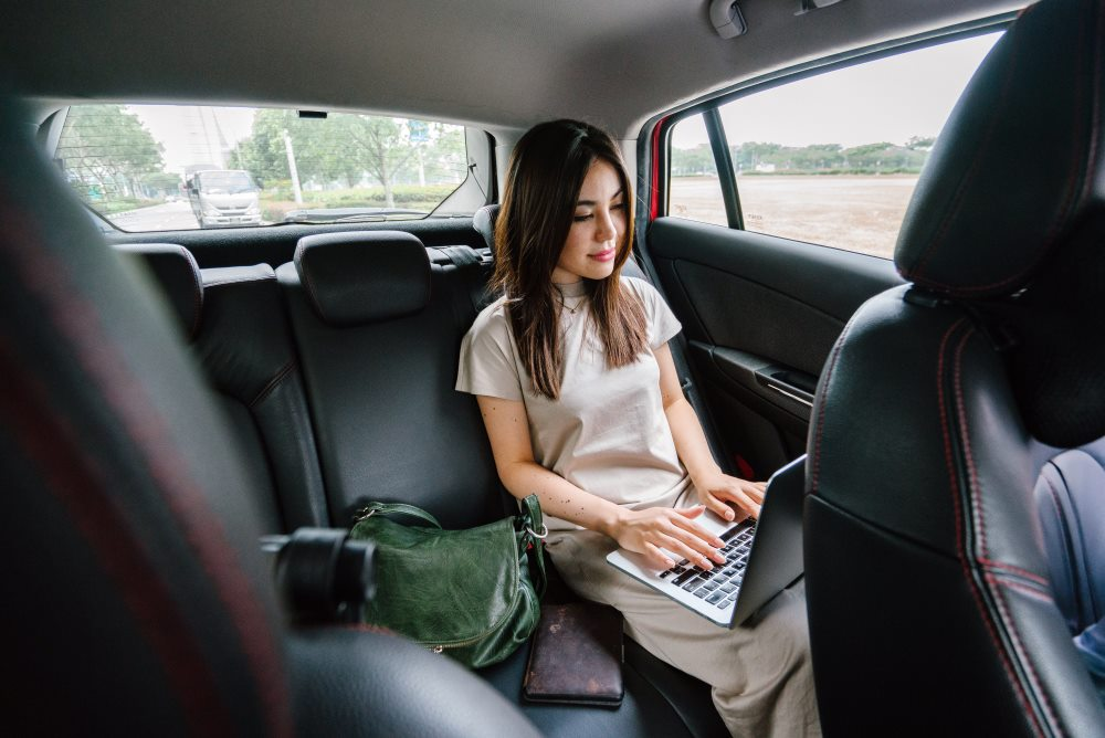woman in car with laptop